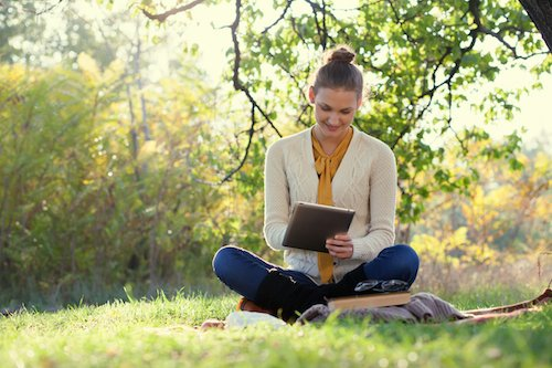 Distance education. Sitting woman using ipad during autumn fun outdoors